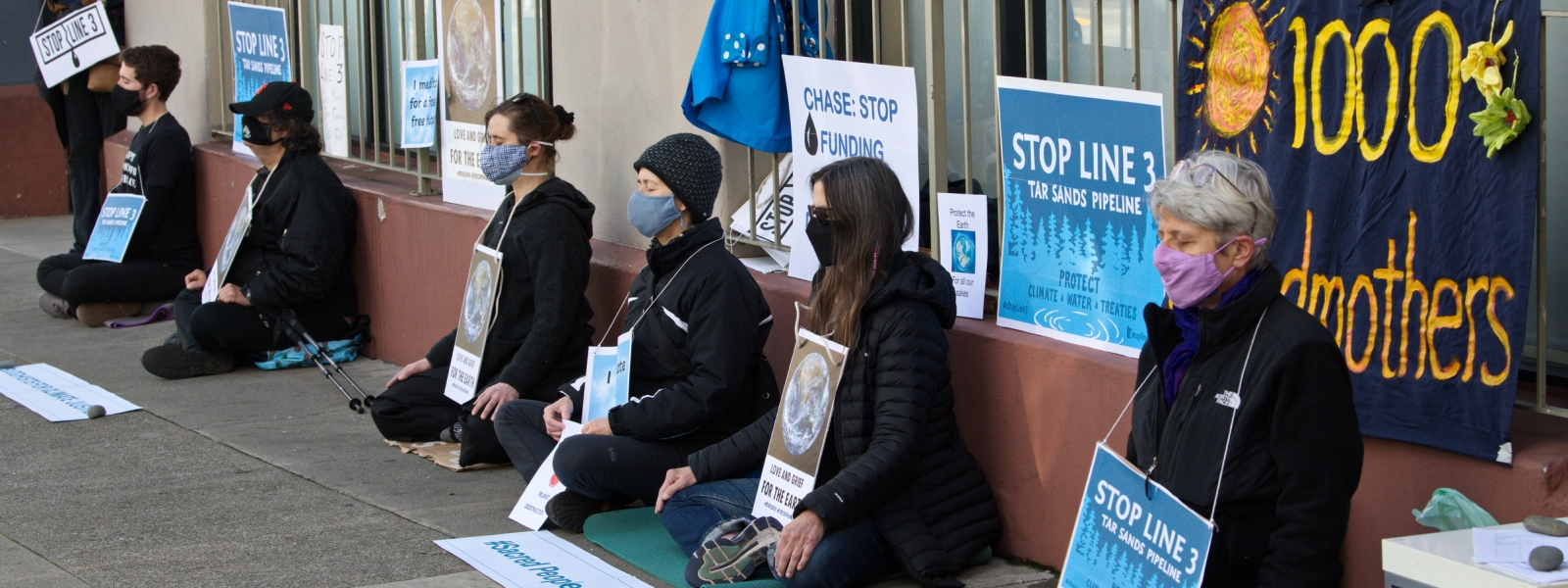 Seven seated meditators on a city sidewalk, wearing various climate-related signs