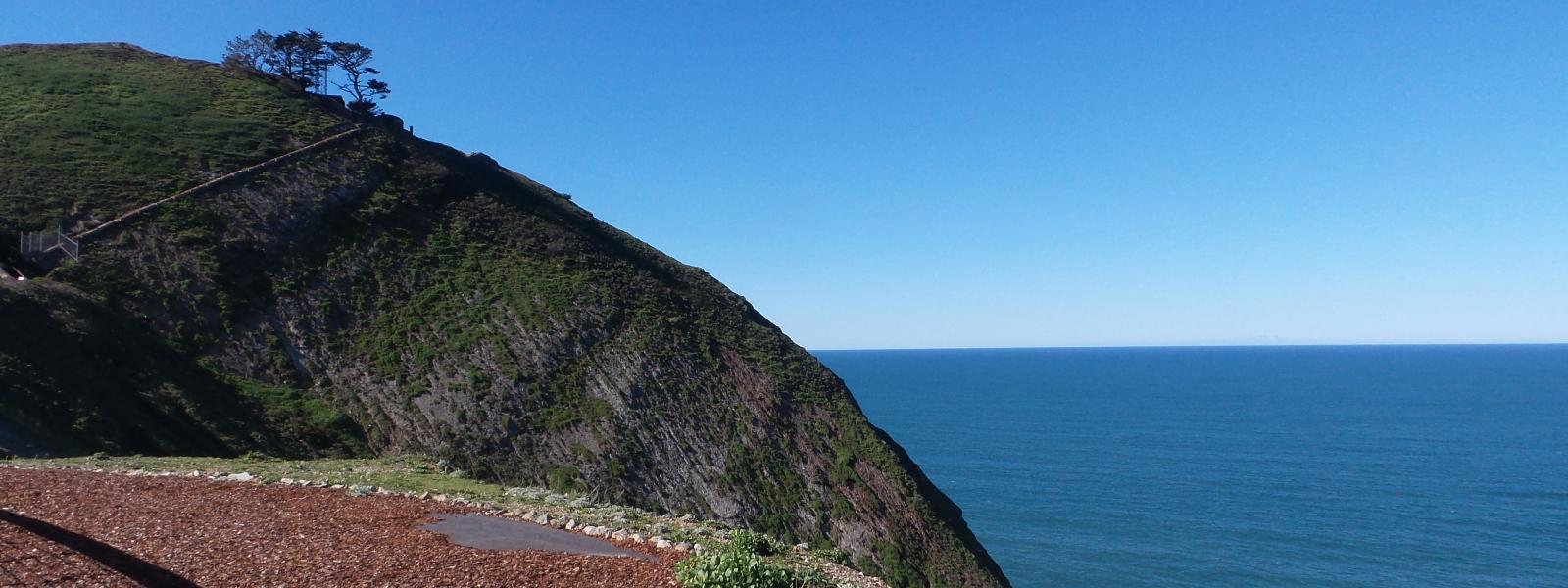 A green coastal hillside and clear blue horizon